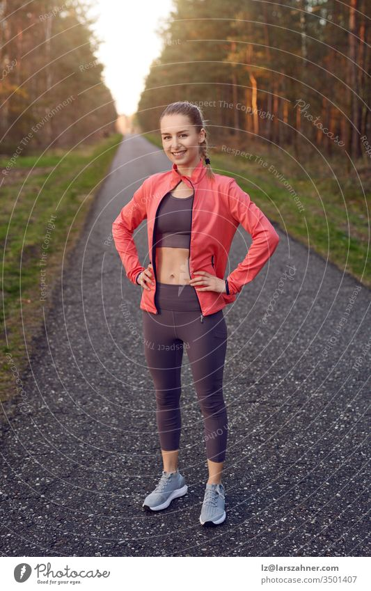 Full length front portrait of sporty young girl in training wear with grey pants and red jacket, standing and resting after jogging with her hands on hips, looking at camera and smiling