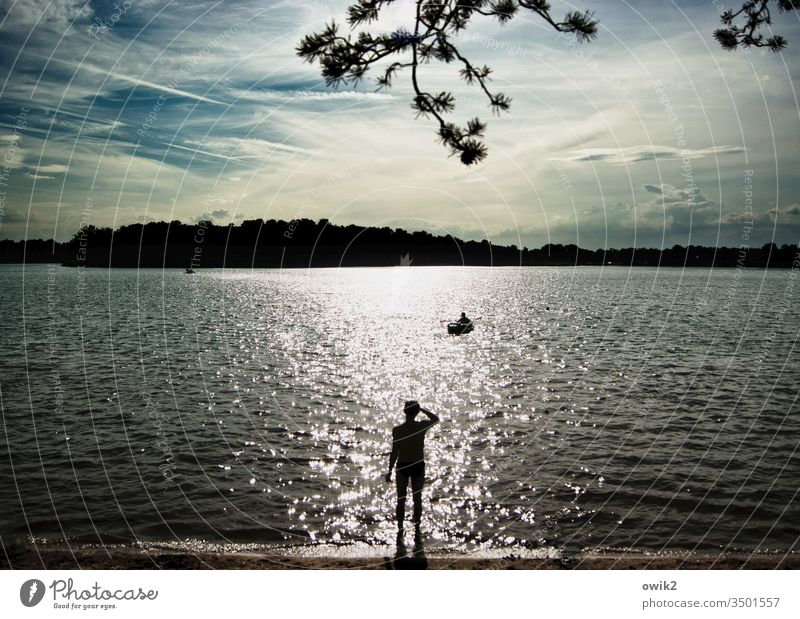 Boy, come back soon. Man Wait Lake Silhouette Twig Sky Island out Longing Sunlight Back-light Shadow Beach Expectation Exterior shot Sunset Light Summer Water