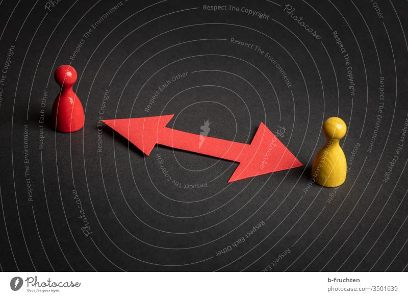 Two game pieces with a red paper directional arrow, black background. Arrow Red Safety gap Piece Black Yellow guard sb./sth. Paper two Couple Couples Direction