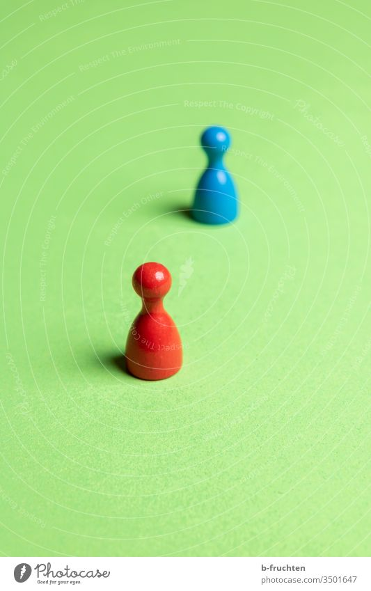 Two game pieces with distance, Social Distance. Piece Red Blue Green gap Close-up Colour photo Toys Playing social distancing social distance Virus Corona virus