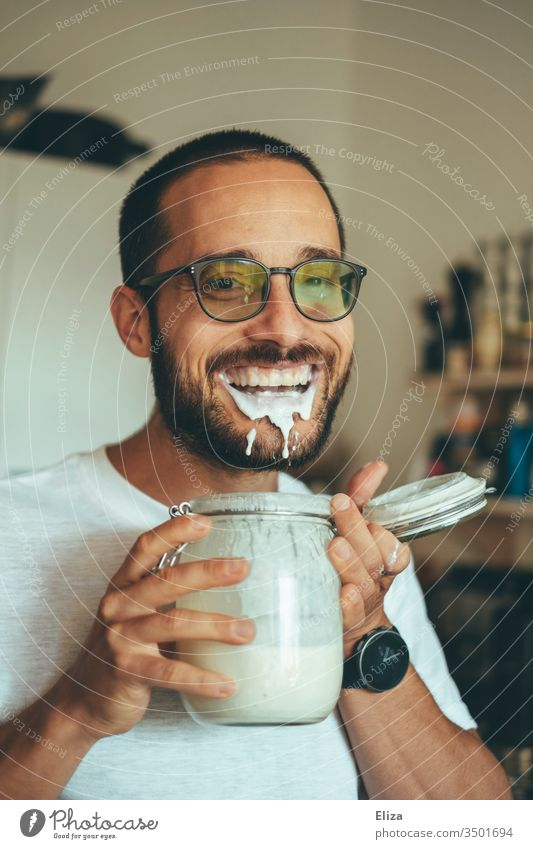 A man is so happy about his homemade kefir full of protein that he only makes nonsense when drinking it and spills it Man Self-made foolish bunkum Drinking