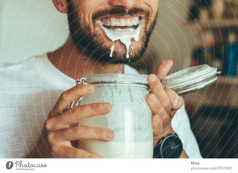 Man is happy about his homemade kefir full of protein and spills and drools around with it Protein high-protein low carb Joy Delicious feast Nutrition Slaver