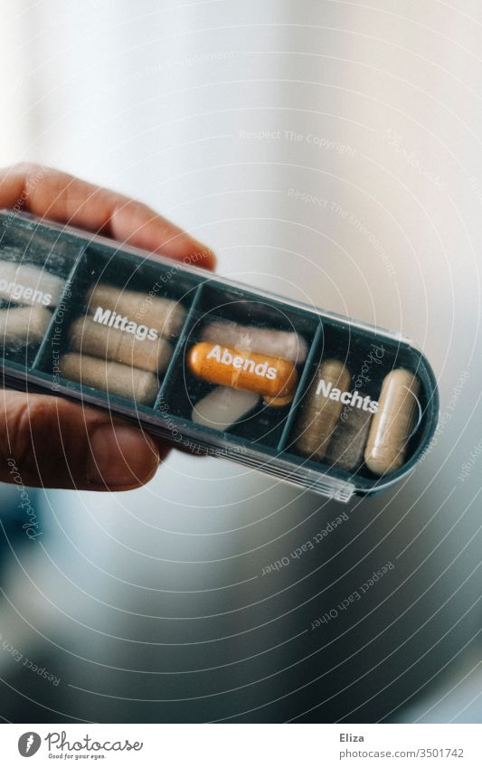A person holds a medicine box in which different tablets and pills are sorted for the different times of day drugs Nutrional supplement diverse Tin pill box
