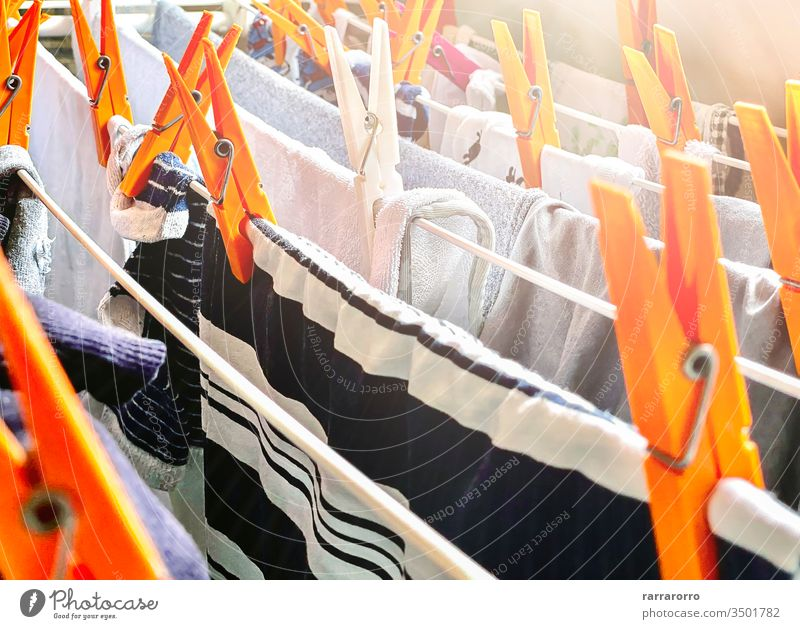 a group of orange clothes pegs on a drying rack to dry the laundry. Clothes hung out to dry inside a house. Housework and hygiene. clothespin clotheshorse dryer