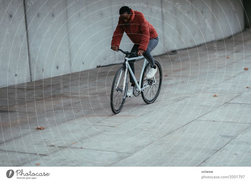 Woman riding bicycle in urban environment cyclist african american on the move lifestyle active transport young eco friendly city city life street young people