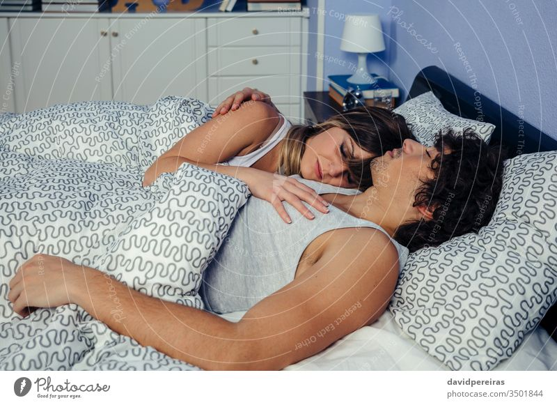 Couple sleeping embraced in bed couple romantic embracing love touching supported reclining peaceful together woman people beautiful caressing hugging home