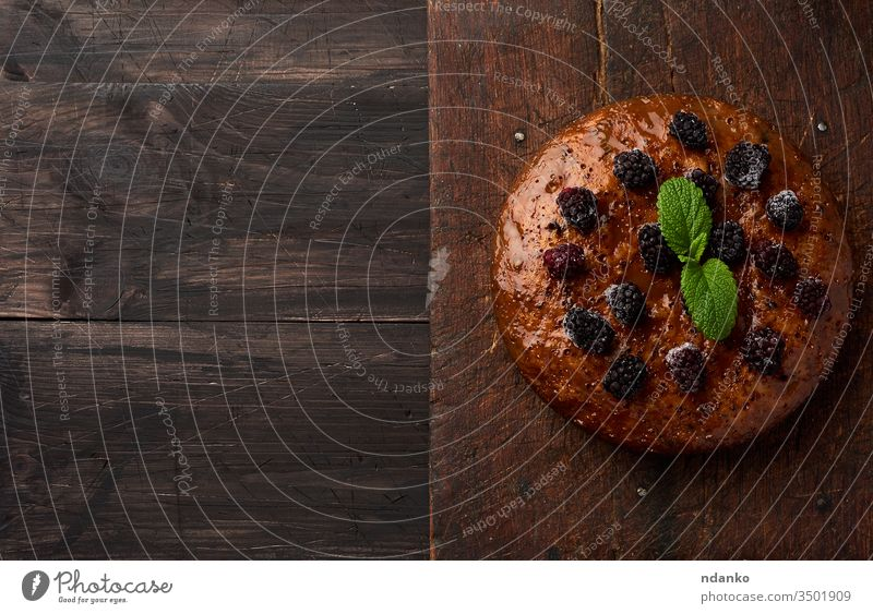 baked round biscuit cake with nuts and berries topped, wooden brown table black bread closeup cook cooking cuisine dark delicious dessert food fresh gourmet