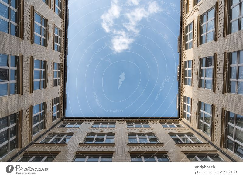 A look up at a white cloud from a courtyard apartment apartments architecture beautiful blue blue sky brick building buildings city clouds construction