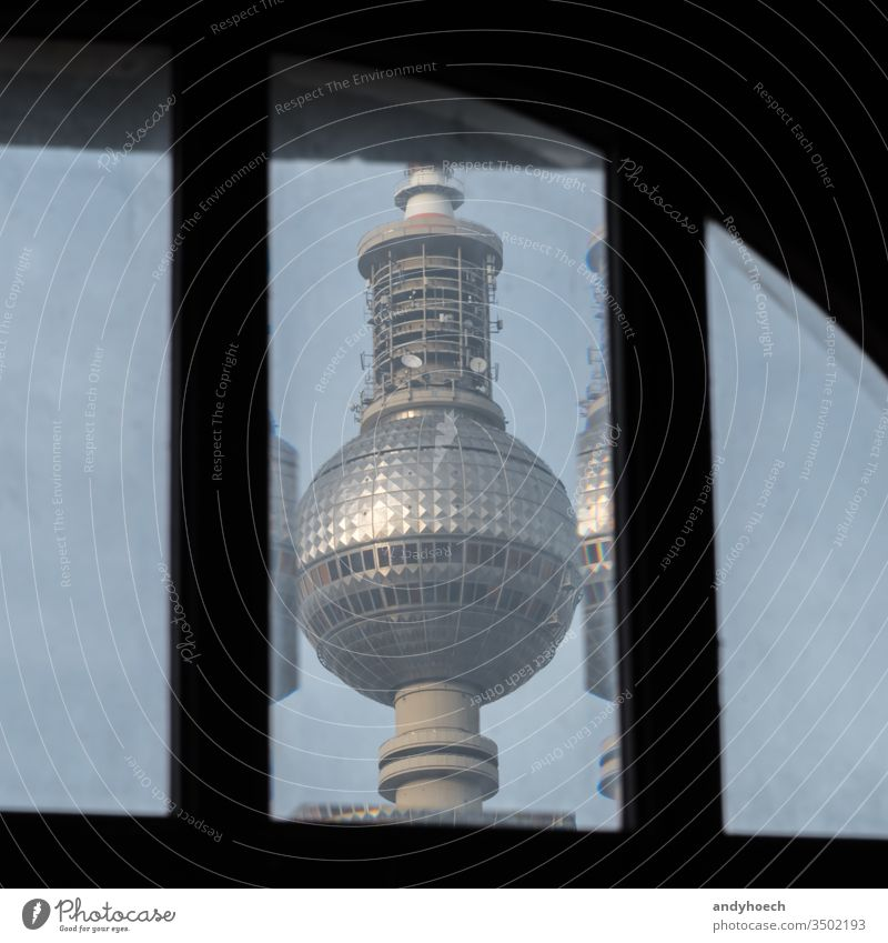 The Berlin TV tower behind an old window alexander Alexanderplatz architecture attraction Background blue broadcast building capital city cityscape