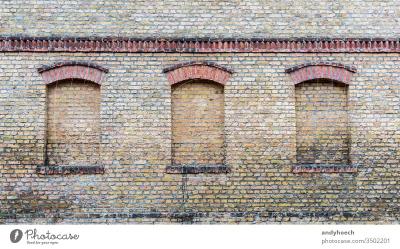 Three windows of an old house are bricked up abstract aged ancient architecture Art Background bricks brickwork brown building Business history closed color