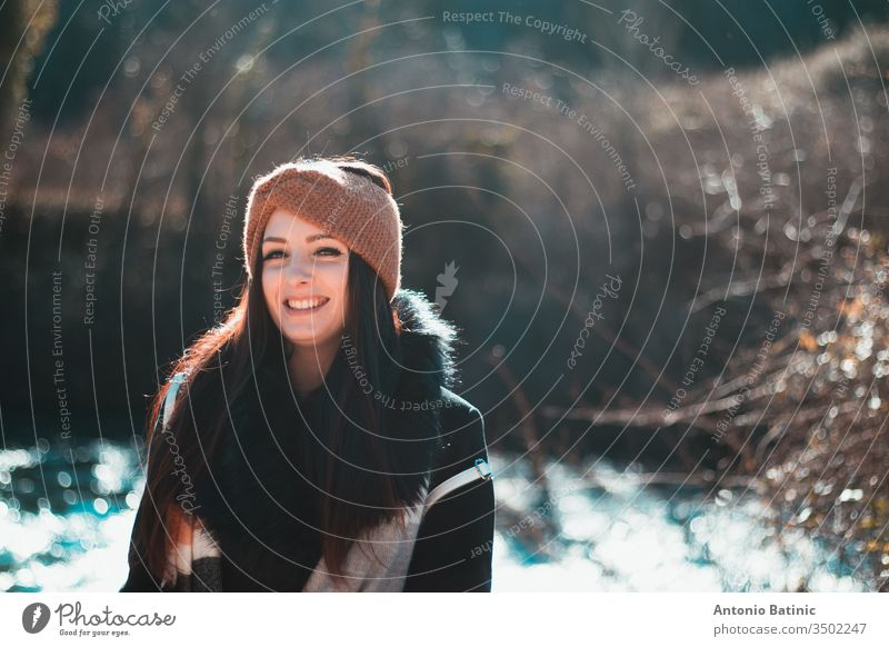 Portrait of an attractive brunette in black winter clothing and an orange headband. Cold winter day in the forest, smiling hapiness adult autumn background