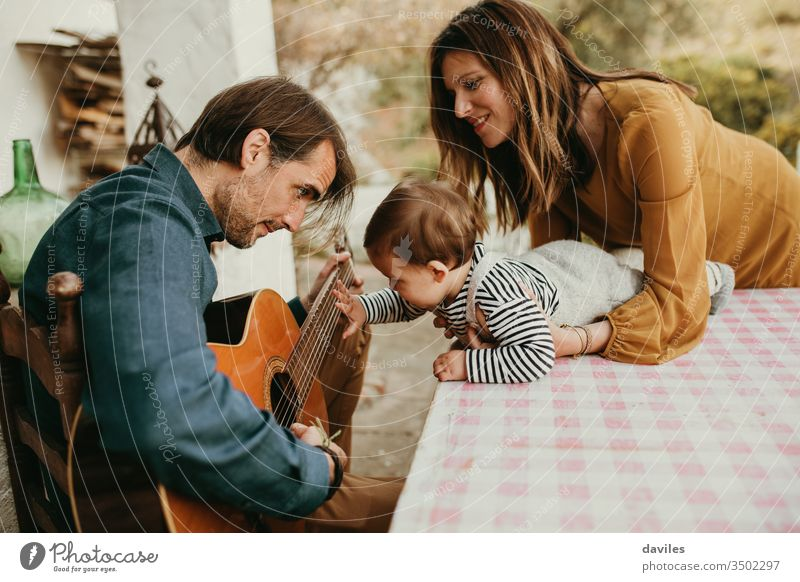One year baby touching his father's guitar while he plays at home courtyard. Mother is holding the baby. small calm garden casual style outdoors white lovely