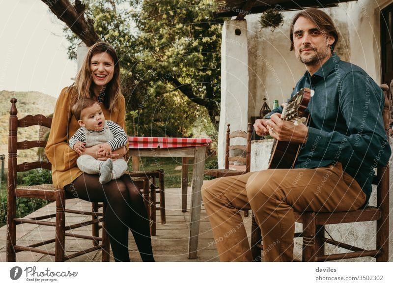 Beautiful couple with their baby infant enjoying sitting on the courtyard at countryside. Man is playing the guitar. Woman holds the baby. They look at the camera.