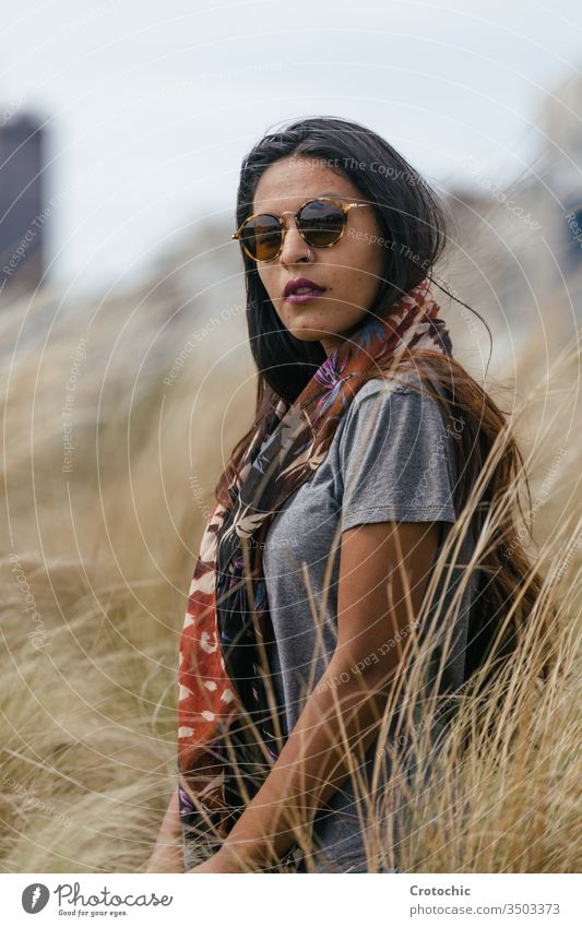 Portrait of a brunette woman with sunglasses wearing a scarf on her neck in a wheat field beauty arab portrait wild turn face facing camera twist hair brown