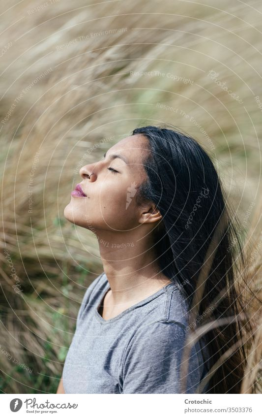 portrait of a young brunette woman with her eyes closed meditating vertical expression face profile dream raising sunlight female field nature comfortable