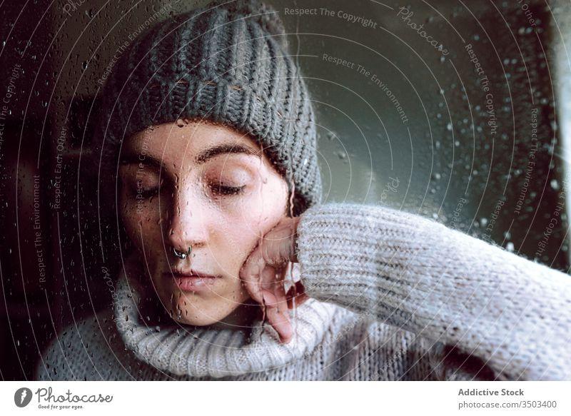 Melancholic young woman looking through window sad depression isolation coronavirus home desperate lonely unhappy female wet rain melancholy solitude stress