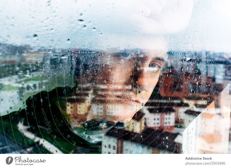 Depressed man looking through window sad depression isolation coronavirus home desperate lonely unhappy young male wet rain melancholy solitude stress frustrate
