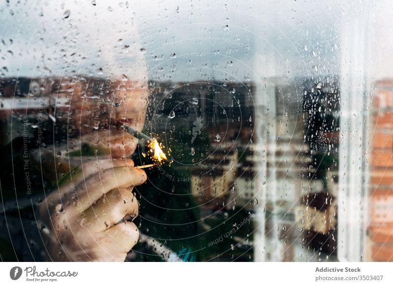 Man smoking cigarette near window at home man smoke lonely sad wet depression coronavirus tranquil self isolation desperate unhappy young male rain melancholy