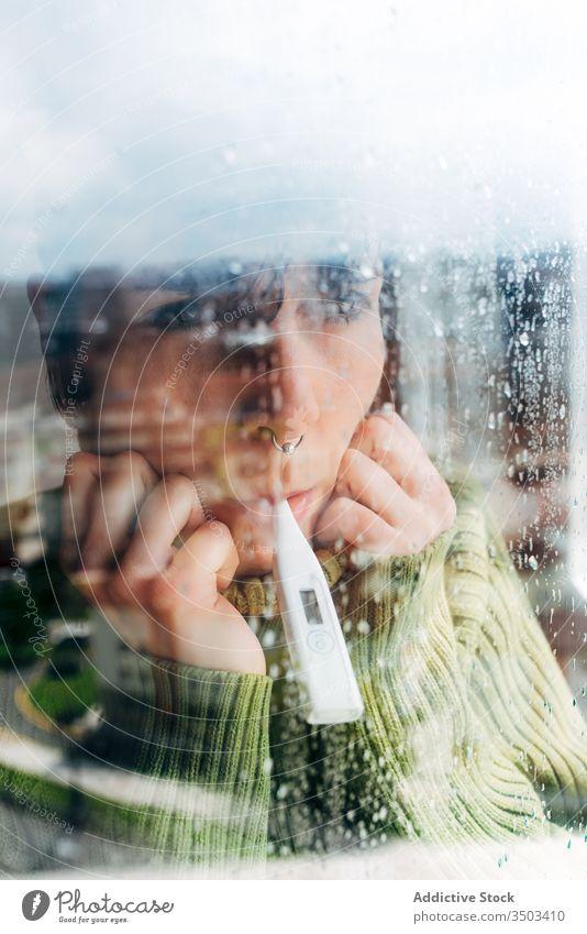 Sick woman checking body temperature near window at home sick thermometer coronavirus isolation fever headache female disease unwell problem cold ill flu pain