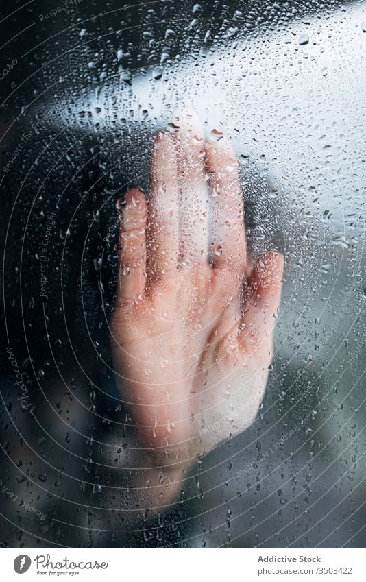 Anonymous person touching glass of window hand home isolation desperate wet coronavirus lonely depression solitude rain problem concept unhappy stress