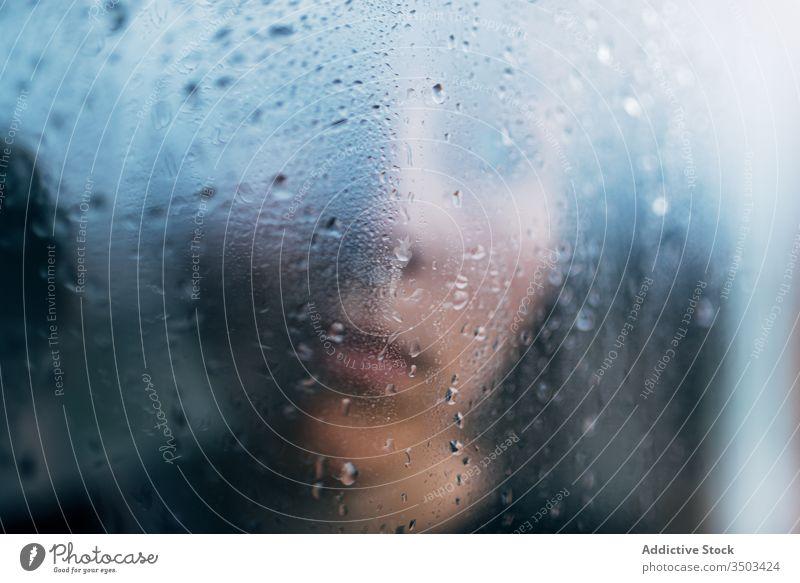 Unrecognizable person standing behind wet glass sad depression isolation melancholy solitude unhappy stress upset lonely rain coronavirus window home desperate