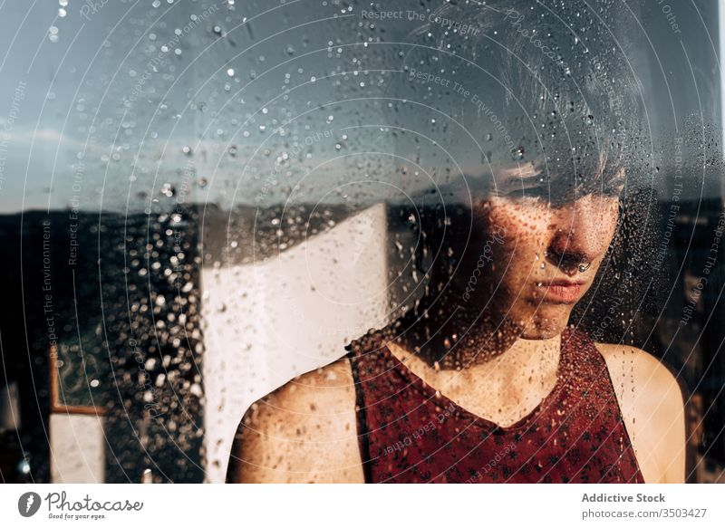Unhappy woman looking through window at home sad lonely unhappy melancholy pensive depression isolation coronavirus young female wet solitude stress frustrate