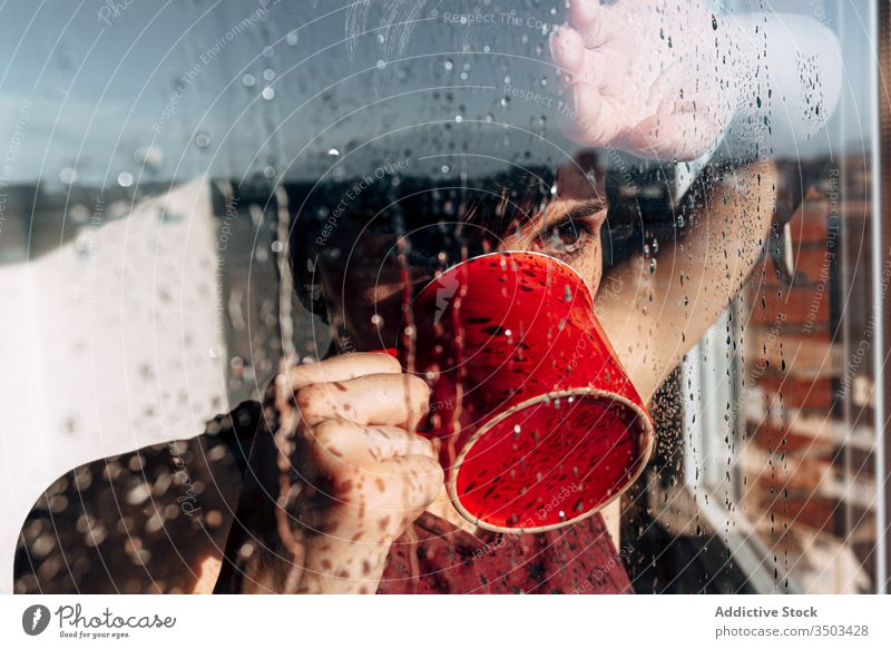 Thoughtful woman drinking coffee near window sad depression self isolation home unhappy lonely covid19 melancholy young female wet rain solitude stress cup