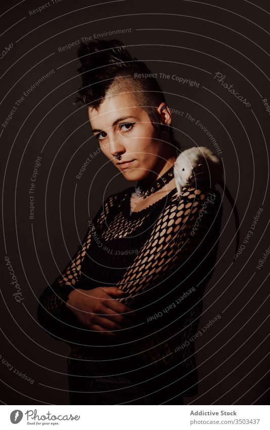 Female punk with rat on shoulder woman style confident pet subculture modern rebel mohawk appearance female dark model piercing individuality personality