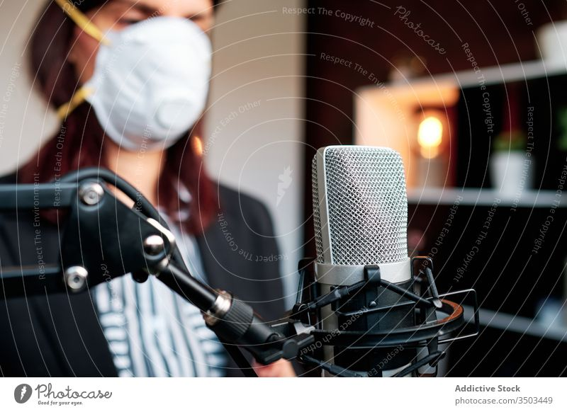 Woman with mask working at home and podcasting with a microphone woman occupation record song presenting speaking networking connectivity explaining learning