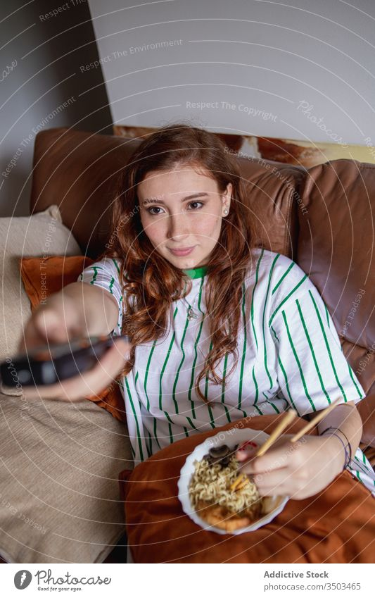 Young female eating noodles and watching TV woman ramen tv home lunch young rest japanese sofa film movie change channel remote control tradition authentic