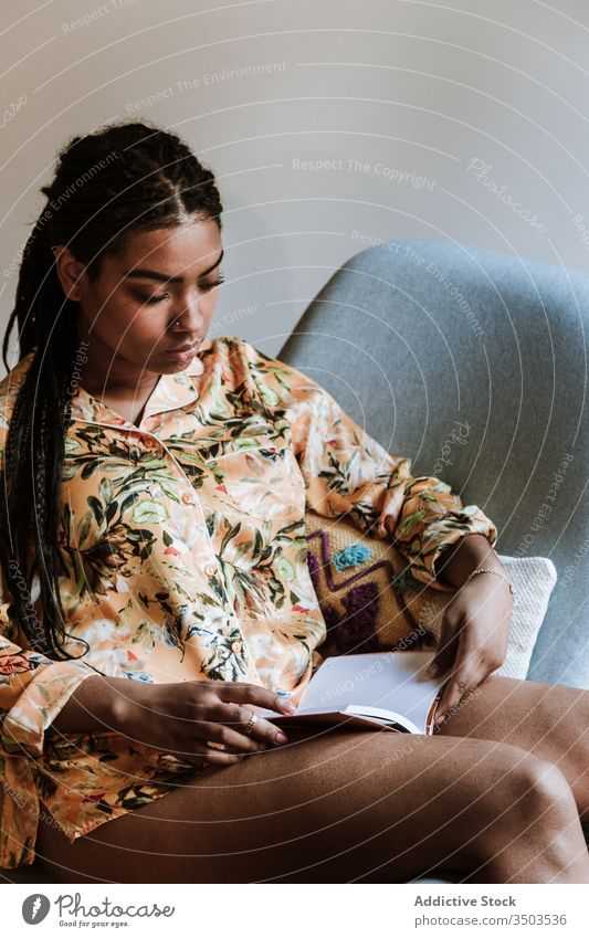 Ethnic woman with book resting at home read african american black casual chair brunette calm sitting young cozy ethnic female free time relax lifestyle