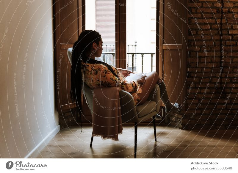 Ethnic woman with book resting at home read african american black casual chair brunette calm sitting young cozy ethnic piercing free time relax lifestyle