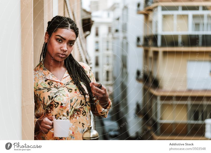Young woman with cup of coffee standing on balcony calm drink casual home tranquil thoughtful relax young african american black ethnic brunette house city