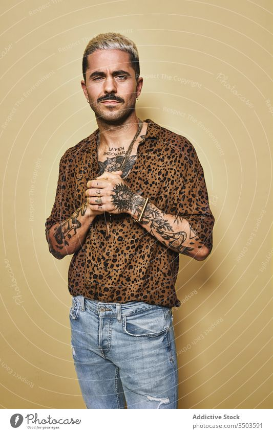 Trendy ethnic guy in stylish outfit standing in studio man trendy style fashion leopard model jeans male cloth modern cool confident handsome contemporary wear