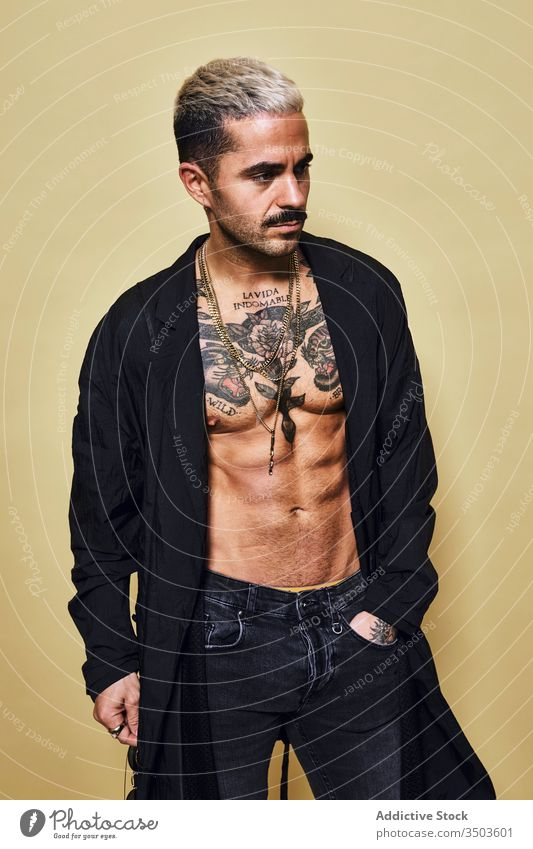 Provocative shirtless man in black coat sunglasses macho cool trendy brutal tattoo style fashion unshaven model personality muscular jeans beard male ethnic