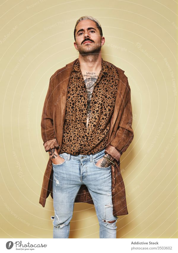 Trendy ethnic guy in stylish outfit standing in studio man trendy style fashion leopard coat model jeans beard male cloth modern cool confident handsome