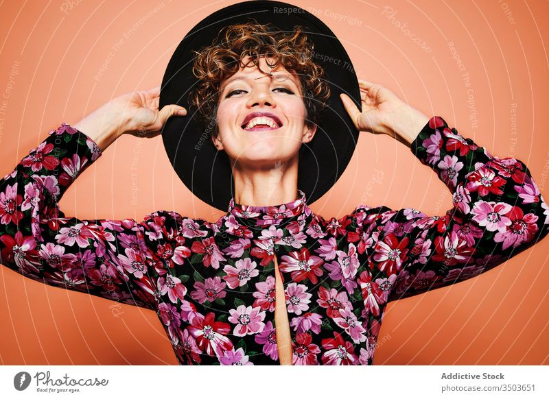 Cheerful woman in stylish outfit fashion cheerful hat colorful floral style trendy smile young female model happy joy bright attractive vivid positive delight
