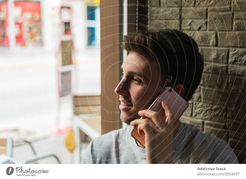 Cheerful young man speaking on smartphone near cafe window smile modern happy call male lean restaurant mobile cheerful chat lifestyle relax guy conversation