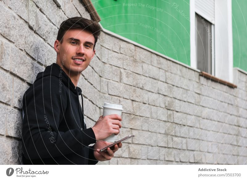 Cheerful man with smartphone and drink to go resting on street using city lean wall positive male building young takeaway beverage cup coffee tea cheerful