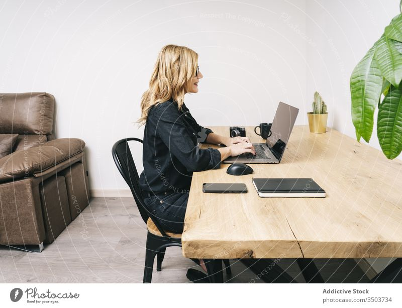 Woman working from her studio office at home woman desk computer business adult eyeglasses laptop caucasian browsing typing businesswoman internet home-office