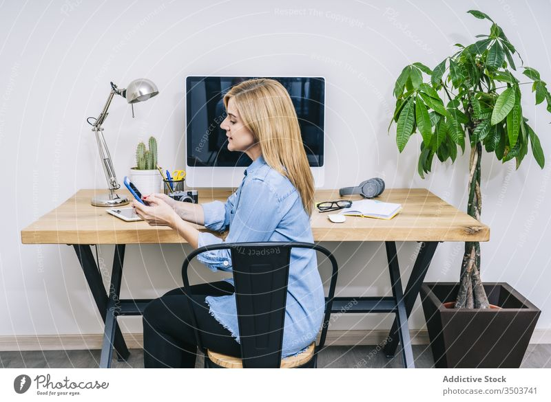 Blonde Caucasian woman works from her home office browsing computer typing desk communication businesswoman tablet indoor adult laptop desktop design lifestyle