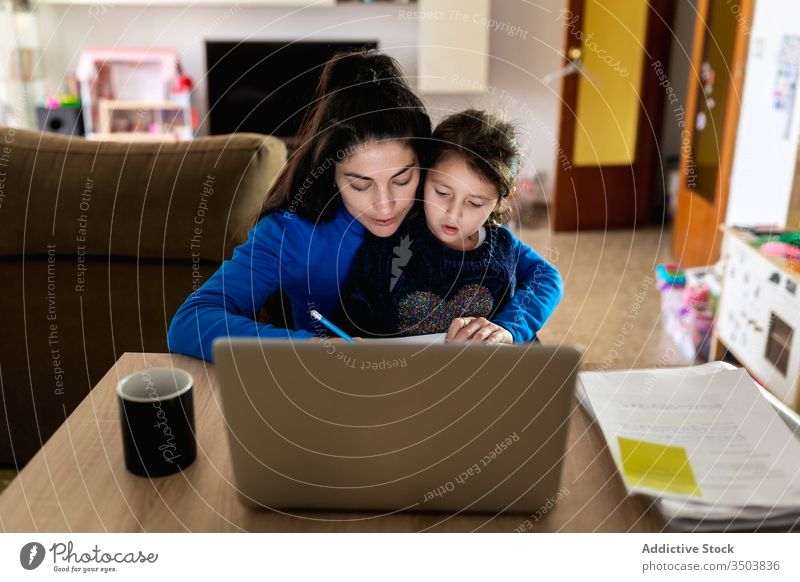 Mother with daughter working on remote project mother freelance home hug read paper laptop table woman girl busy child kid together device gadget document