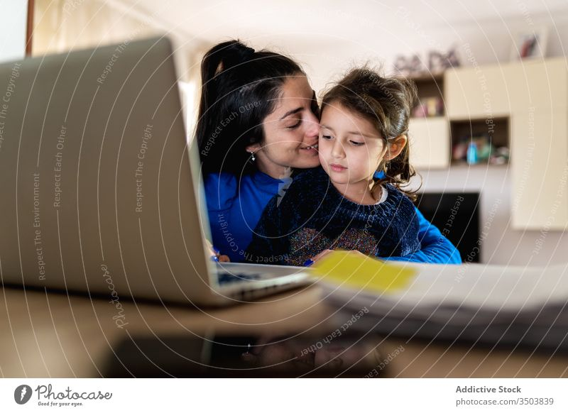 Mother playing with daughter and working on remote project mother hug laptop using home bother love woman girl little freelance child kid parent together