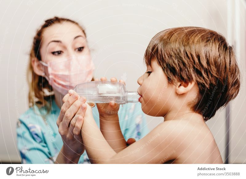 Little kid using inhaler in clinic during check up child respiration sick treat respiratory medicine medical doctor mask little woman hospital health care
