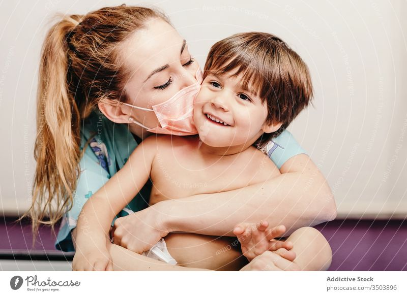 Happy woman in medical mask kissing kid happy patient clinic kind love hug prevent protect virus together cheerful young female cute little son child care smile