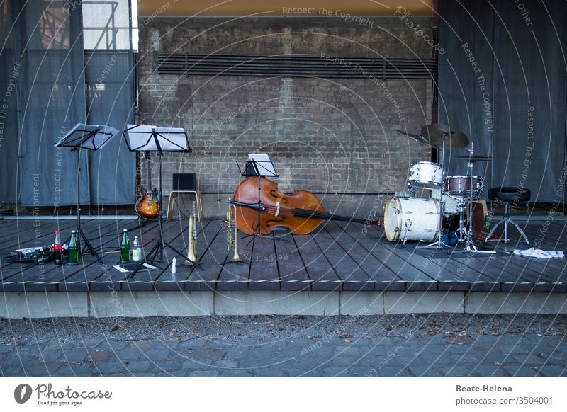 deserted concert stage with music stands, guitar, trumpet, double bass and drums Deserted Guitar Double bass Drum set Drink bottles Music Concert Shows