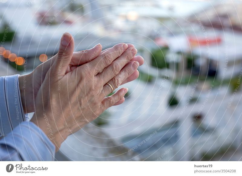 woman's hands on the balcony to applaud medical staff for the fight against the coronavirus covid-19 applause appreciation clap window terrace quarantine