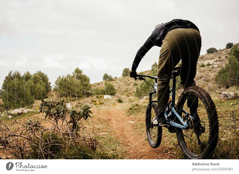 Cyclist riding bike on rocky path in forest man bicycle ride tree travel cyclist helmet male trip journey activity recreation route vehicle transport lifestyle