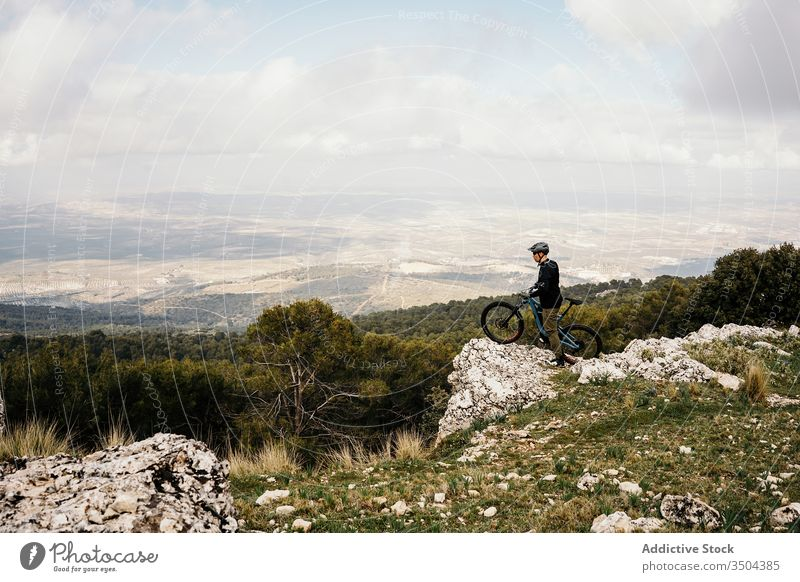 Cyclist riding bike on rocky path in forest man bicycle ride tree travel cyclist helmet trip journey activity recreation route vehicle transport lifestyle