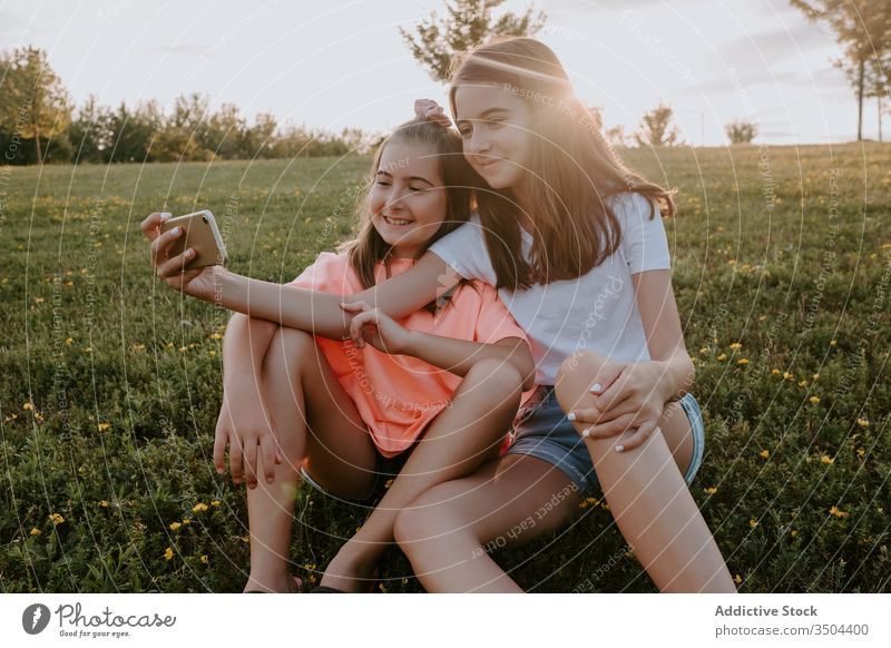 Adorable sisters sitting in a park and taking a selfie kid nature together happy hug grass summer girl countryside cheerful teen teenage green meadow sibling